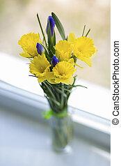 Flowers in vase on white window sill
