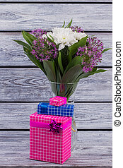 Flowers in vase with gift boxes.