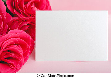 Flowers mock up congratulation. Congratulations card in bouquet of pink red roses on pink background. White blank card with space for text, frame mockup. Spring festive flower concept, gift card.