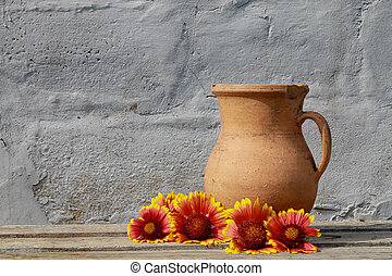 Flowers near the old ceramic jug on