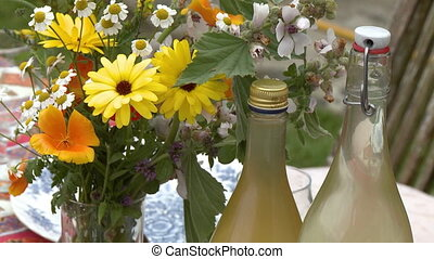 Flowers Next To Glass Bottles