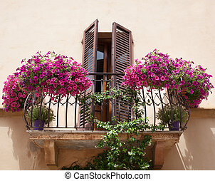 Flowers on a balcony in Pienza Tuscany, Italy.
