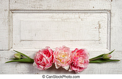 Flowers on a paneled vintage door, (pink tulips or rose like...