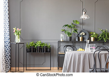 Flowers on black table against the wall with molding in grey restaurant interior with lamp. Real photo