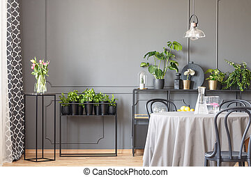 Flowers on black table next to plants in grey dining room interior with chairs and lamp. Real photo