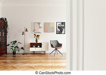 Flowers on cupboard between gold lamp and grey chair in white apartment interior with plant. Real photo
