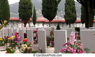 Flowers on graves in Italian cemetery - Light breeze moving ...