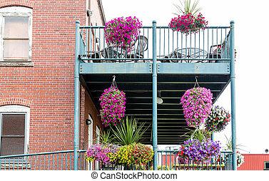 Flowers on Metal Balcony of Brick Building