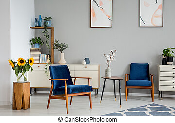 Flowers on table between blue armchairs in living room interior with posters and sunflowers. Real photo
