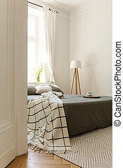 Flowers on table next to bed in bright bedroom interior with basket and window. Real photo