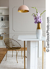 Flowers on white marble table near gold chair under pink lamp in grey dining room interior. Real photo