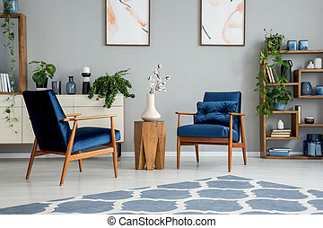 Flowers on wooden table between blue armchairs in grey flat interior with carpet and posters. Real photo