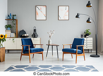 Flowers on wooden table between blue armchairs in living room interior with posters. Real photo
