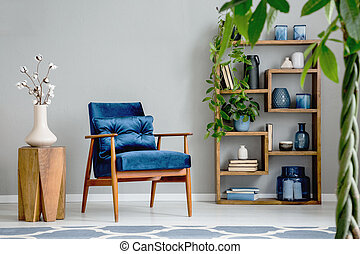 Flowers on wooden table next to blue armchair in grey living room interior with plants. Real photo