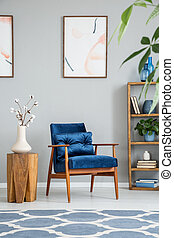 Flowers on wooden table next to blue armchair in grey living room interior with posters. Real photo
