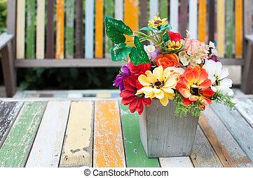 Flowers vase put on the old paint wood table