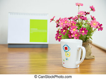 flowers with coffee cup on workspace.