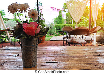 Flowers with old vase on wooden table at coffee shop.