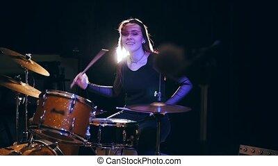 Flowing black hair - beauty girl plays drum rock at garage,...