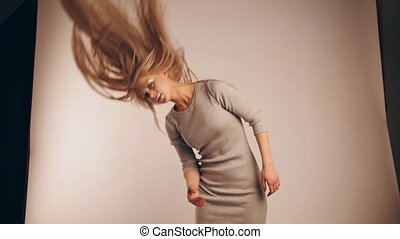 Flowing hair of attractive model girl in photo studio, slow-motion