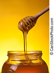 Flowing honey over yellow background