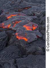 Flowing lava in Hawaii - Surface flow lava oozes out of the...