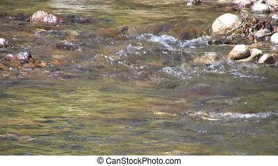 Flowing Mountain Stream - a mountain stream flows over rocks