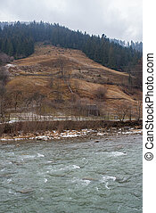 Flowing river in the winter Carpathian mountain