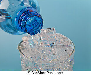 Flowing water in a glass with ice from a bottle on a blue background