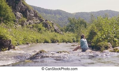 Flowing water of mountain rivera and woman sitting on stony...