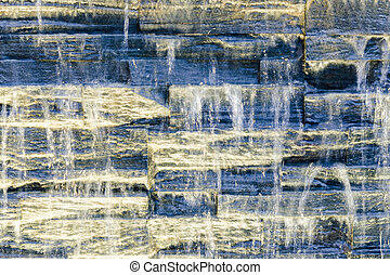Flowing water over dark stone wall