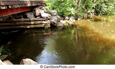 Flowing water under the wooden bridge