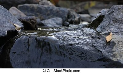 Extreme close-up of river water flow. Water flows down the stones. Untouched nature and sacred water. A tranquil scene of flowing water