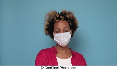 Flu concept. Young african woman putting on and off protective face mask, blue studio background