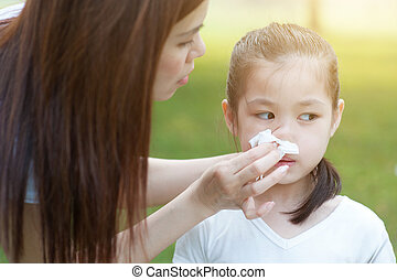 Flu season, little girl blowing nose.