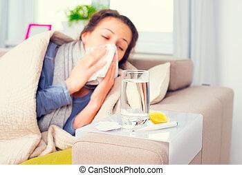 Flu. Sick woman sneezing into tissue