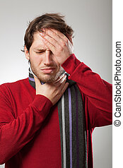 Flu symptoms - Man in red sweater and scarf has a strong flu...