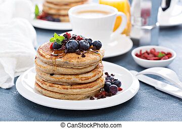 Fluffy chocolate chip pancakes on breakfast table