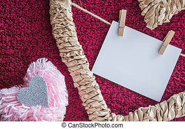 Fluffy pink pompom and braided frame in the form of a heart with a card on the clothespins