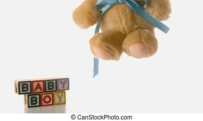 Fluffy teddy bear falling besides blocks spelling baby boy
