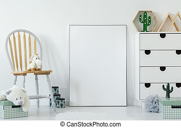 Fluffy toy placed on wooden chair in white baby room interior with cupboard with decor, boxes and mockup poster. Paste your graphic here