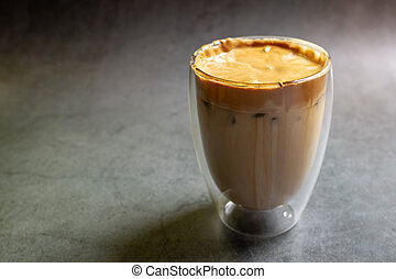 Fluffy whipped coffee on milk. Coffee is a beverage made by whipping equal proportions of instant coffee, sugar and hot water until it becomes creamy.