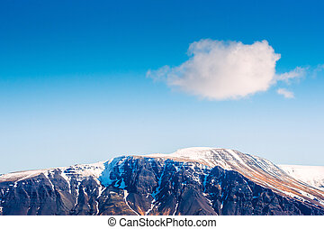 Fluffy white cloud over a mountain top