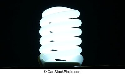 fluorescent lamp turning on and off on black background, slow motion.