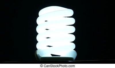 fluorescent lamp turning on and off on black background, slow motion