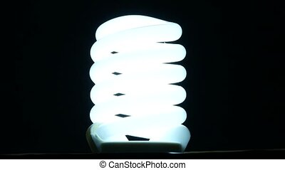 fluorescent lamp turning on and off on black background,...