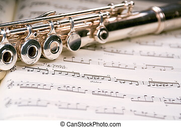Flute across a musical score - A used flute rests across an...