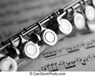 flute and music score - flute on a music score sheet
