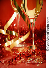 Fluted champagne glasses and ribbons on red background