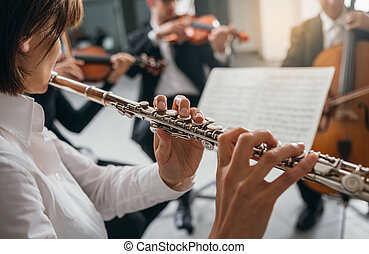 Flutist playing her instrument on stage - Professional...